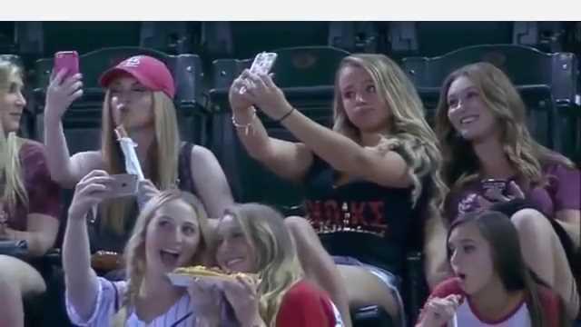 野球観戦そっちのけで自撮りに夢中な女子学生